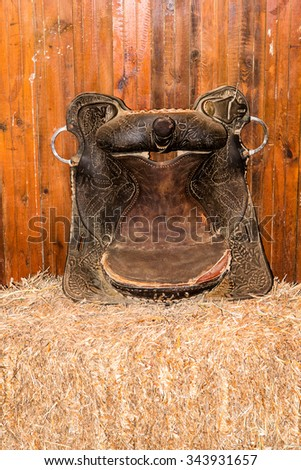 old leather saddle is like a decoration on a pile of hay - stock photo