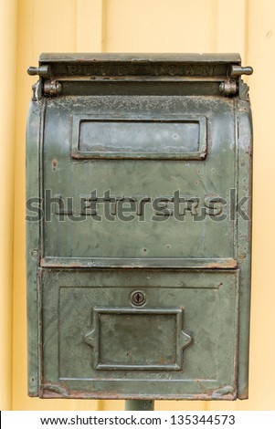 old letters box on yellow wooden wall - stock photo