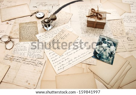 old letters, vintage postcards and antique feather pen. nostalgic sentimental background with retro picture of couple - stock photo