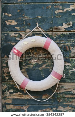 Old life saving ring on wall - stock photo