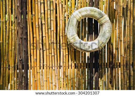 old lifebuoy at the bamboo fence - stock photo