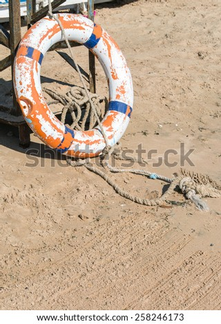 Old lifebuoy on the sandy beach - stock photo