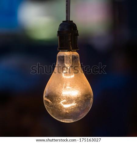 old light bulb glowing in dark - stock photo