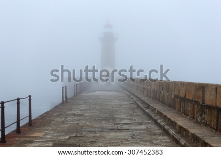 Old lighthouse and pier in a foggy early morning - stock photo