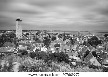 Old lighthouse in a small village on the island Terschelling in the Netherlands - long exposure shot (black and white) - stock photo