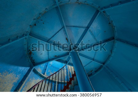 Old lighthouse on the inside. Red iron spiral stairs and blue wall. Kihnu, small island in Estonia. Europe - stock photo