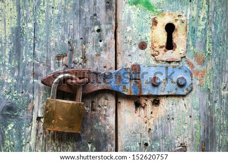 Old lock and rusted keyhole on green wooden door - stock photo