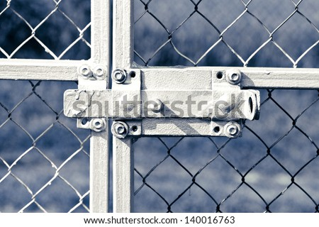 old lock on metal fence - stock photo