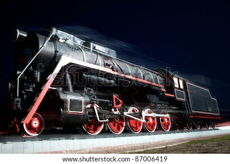 old locomotive is moving in the night - stock photo