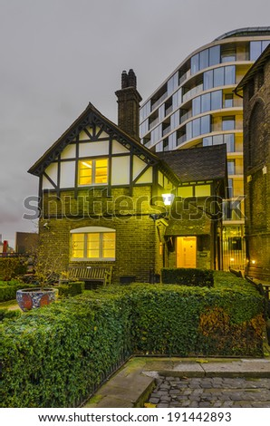 old london house near Tower of London with view of new buildings at background. Night shoot, London, UK - stock photo