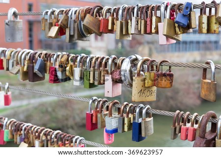 Old love padlocks hanging from railing of Kettenbrucke bridge in Bamberg, Germany. - stock photo