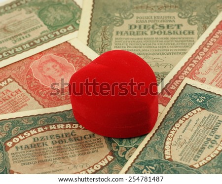 Old love: red heart shaped jewelery box on old, historical Polish notes, bills from Second World War. Focus on some part of the image only - rest is blur by intention. - stock photo