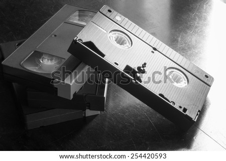 Old magnetic films on old table black and white - stock photo