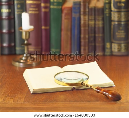 old magnifying glass with open book and candle - stock photo