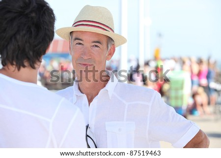 Old man and son stood by port - stock photo