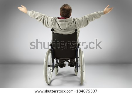 old man and wheelchair in gray studio  - stock photo