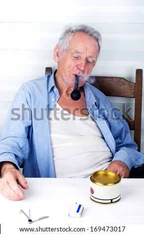 Old man bohemian enjoying smoking pipe  - stock photo