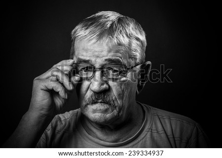 old man corrects glasses - stock photo