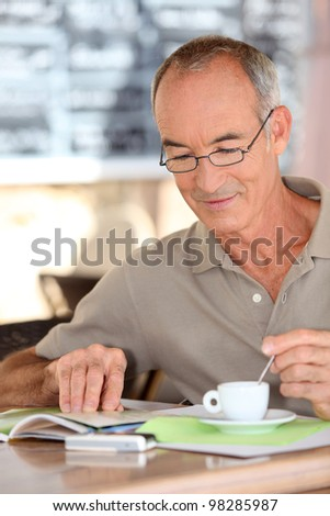 Old man drinking coffee and reading - stock photo