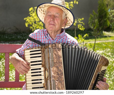 Old man enjoying playing accordion in his garden on sunny day - stock photo