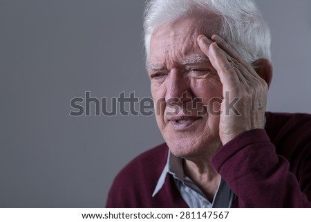 Old man feels pain in his temples - stock photo
