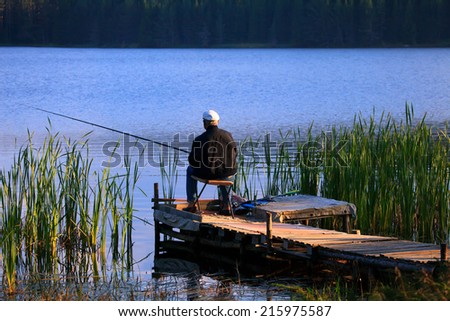 old man fishing from the key in high mountain blue lake, sunset golden hour  - stock photo