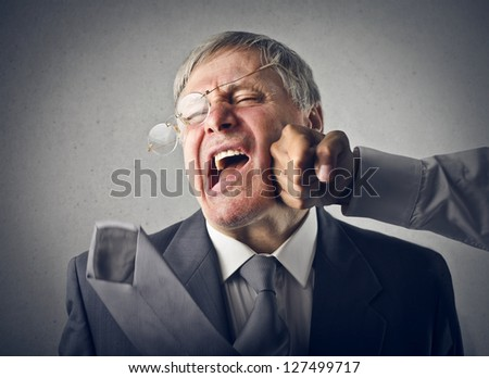 old man gets a fist on the cheek - stock photo