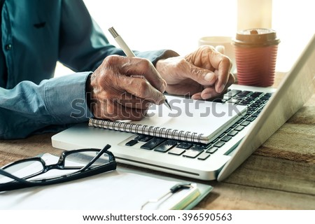 old man hand writing with a pen in a notebook,Handwriting  on office wood table with laptop computer - stock photo