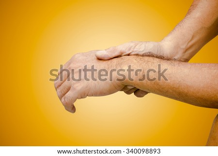 Old man has pain in wrist - stock photo