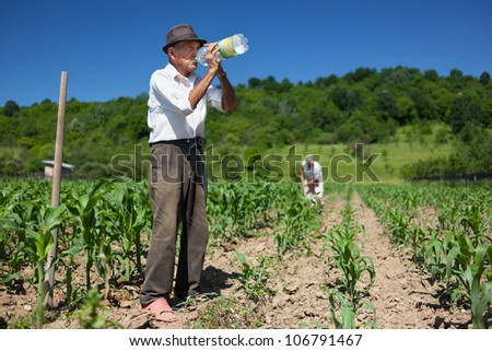 Old man having a break from work, drinking water - stock photo