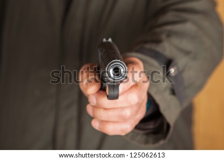 old man hold a pistol pointing to the camera - stock photo