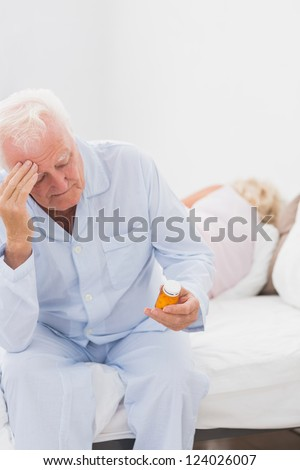 Old man holding pills while woman sleeping on the bed - stock photo