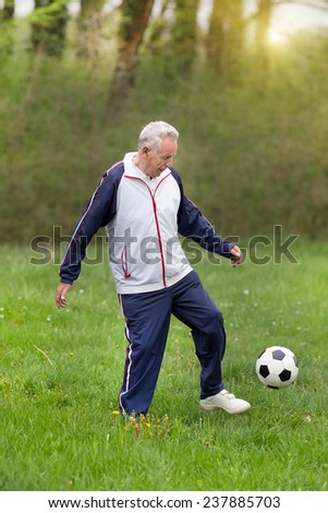 Old man in seventies kicking a soccer ball in park - stock photo