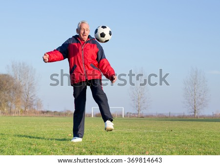 Old man in seventies kicking a soccer ball on playground - stock photo