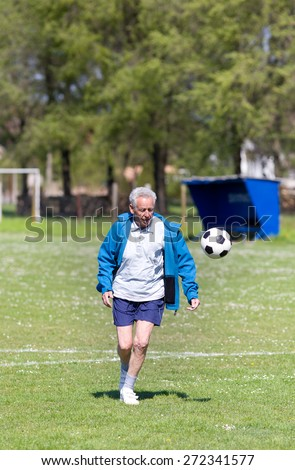 Old man in seventies kicking a soccer ball on the field - stock photo