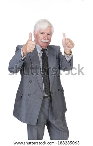 Old man in suit and gray hair with both hands showing thumbs up looking at the camera - stock photo