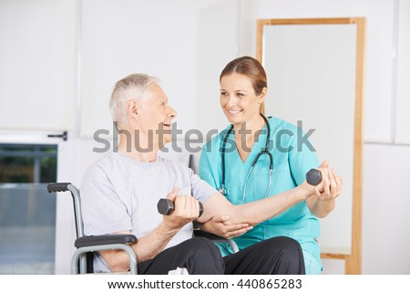 Old man in wheelchair lifting dumbbells in physiotherapy - stock photo