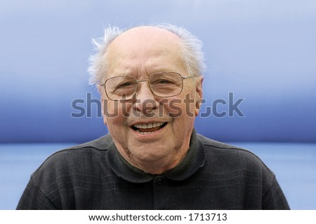 Old man laughing on a blue background - stock photo