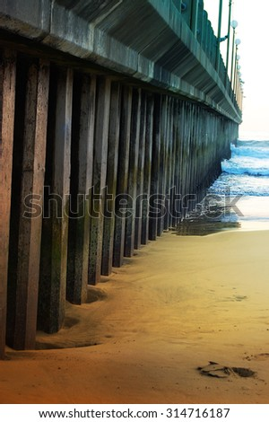 old man made pier extending into ocean from beach - stock photo