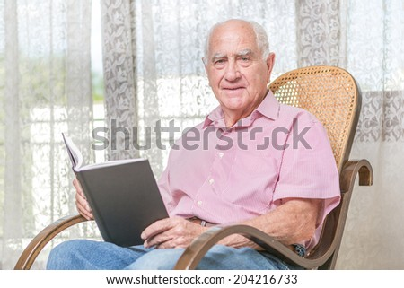 old man reading a book at home - stock photo