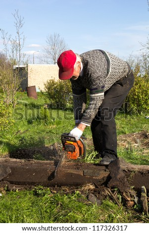 old man saw log with a chainsaw in the garden - stock photo