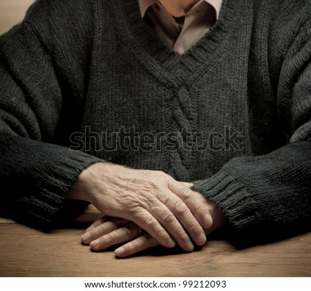 Old man sitting at a table with dramatic lighting - stock photo