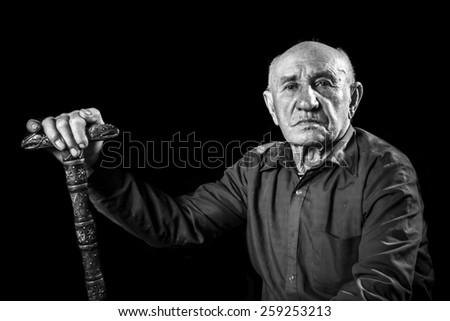 old man sitting with a stick - stock photo