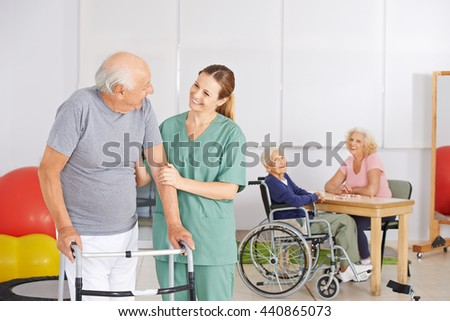 Old man standing with geratric nurse in nursing home with senior people - stock photo