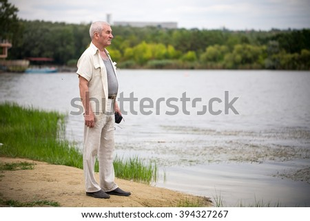 Old man staying near park lake. Photo can be used as a whole background. - stock photo