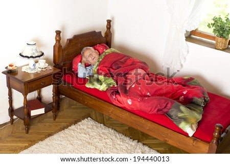 Old man taking a nap with open mouth in his bed - stock photo