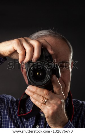Old man taking a picture - stock photo