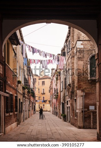 Old man taking some pictures of empty street in Venice. Creative long time landscape photography. - stock photo