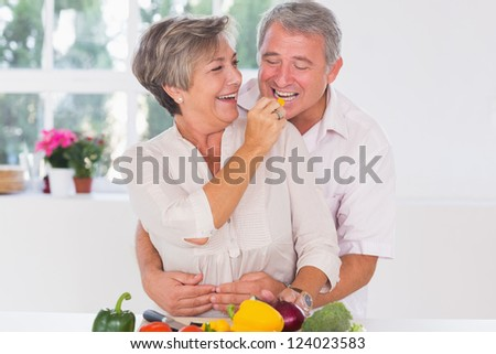 Old man tasting vegetable held by wife in kitchen - stock photo