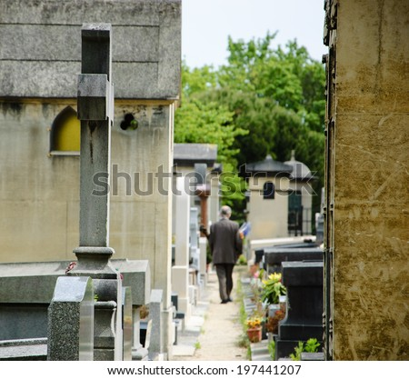 Old man walking in Montparnasse Cemetery in Paris (France). Rear view. Selective focus on the cross and tomb at foreground.  - stock photo